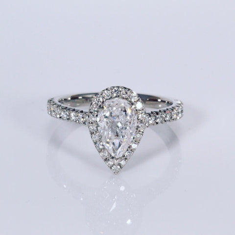 1ct pear shaped halo in platinum an white background