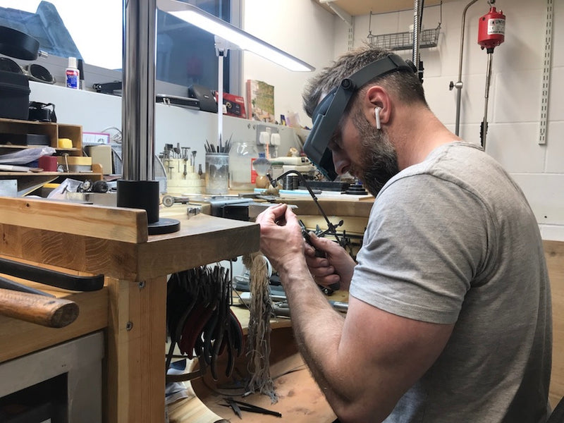 Jeweller working at jewellery bench cuts metal using saw frame