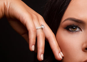 Dark haired woman displays diamond engagement and wedding rings near her pretty face