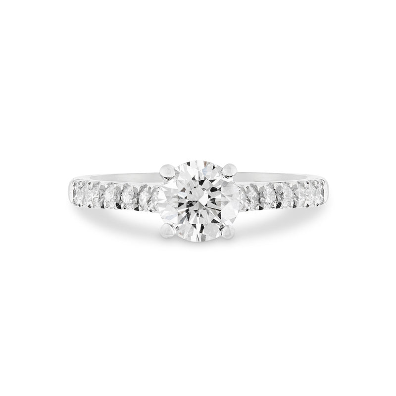 Round diamond 4 claw platinum engagement ring with micro diamond shoulders lays on a white background