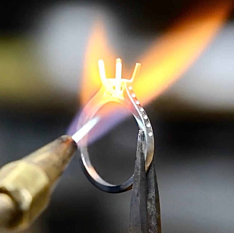 A platinum ring is being heated with an blue and red flame in a London jewellery studio.