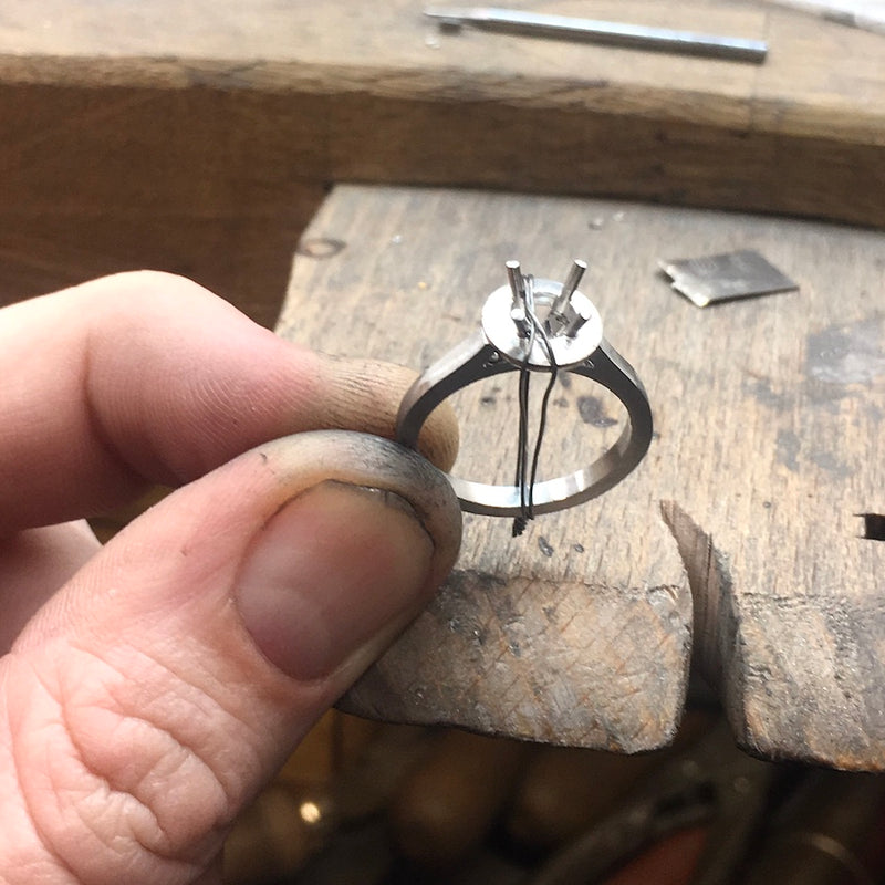 Platinum Halo engagement ring work in progress held by jewellers fingers at a London jewellers bench pin