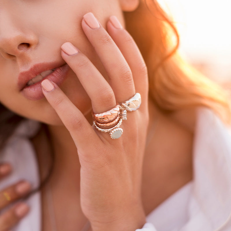 Girls hand on face with sun behind her. wearing designer gold, silver and aquamarine wave rings.