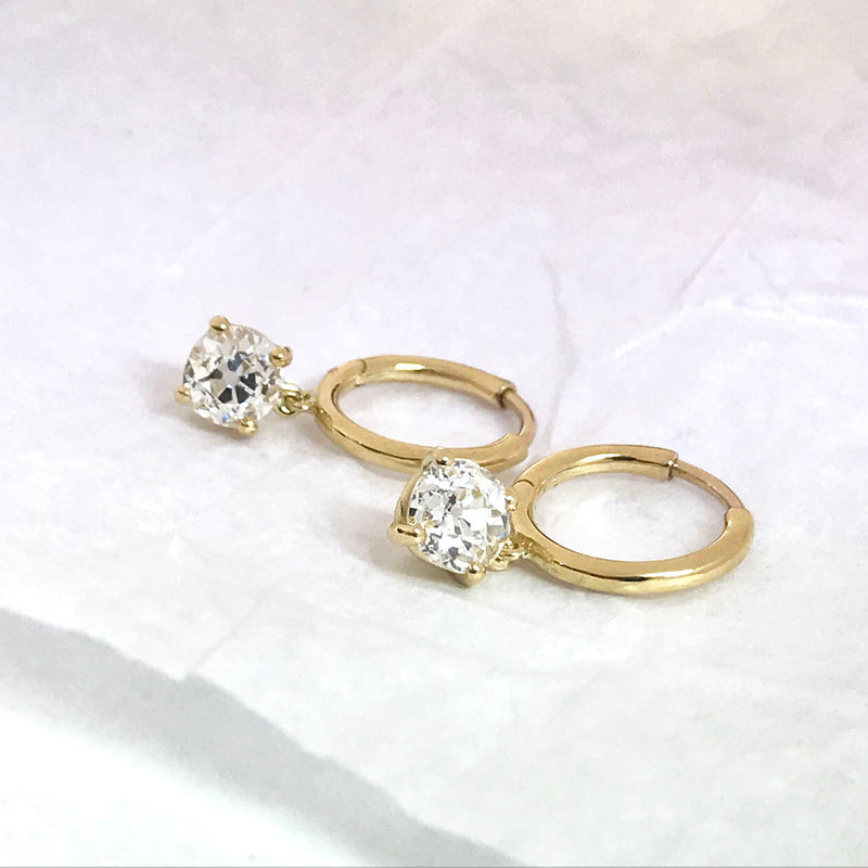 Yellow gold hoop earrings with old cut diamond drops. Laying on white tissue.