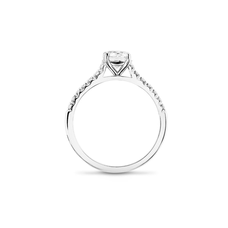 Side view of a diamond 4 claw platinum engagement ring with diamond shoulders stands on a white background