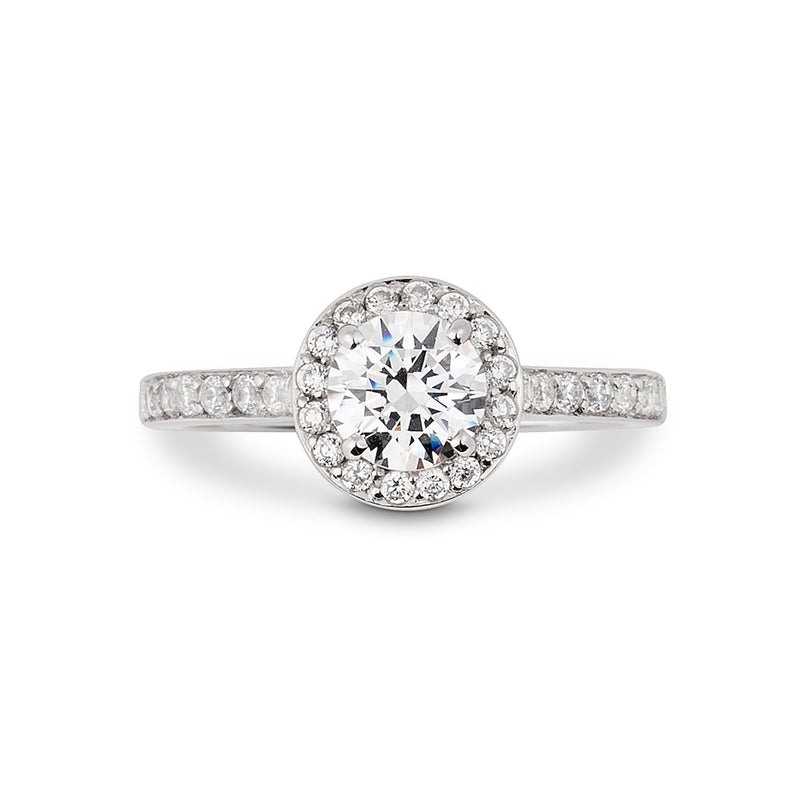 Brilliant cut diamond platinum Halo style engagement ring lays on a white background