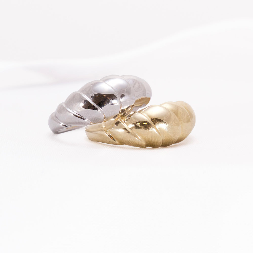 White and yellow gold contemporary rings with wave design on a white background