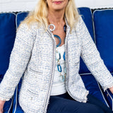 Indigo Tweed 3/4 Sleeve Jacket By Patty Kim.This beautiful tweed jacket Chanel style is fully lined and is ornate with pearl buttons. Fringes on the bottoms add interest. A very elegant garment to complete your summer wardrobe.