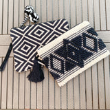 "Ziptop embroidered or weaved clutches with a tassel or pompoms. Lined.  Practical beach or summer accessory with a touch of fun.  Embroidered diamond clutch with a black tassel 12"" x 8""  Weaved diamond pattern with black/white pompoms 13"" x 9""by Two b's accessories"