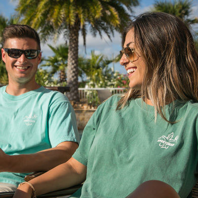 Sportsman light blue and green Short Sleeve Shirts - Classic Logo - White Deer, Duck, Fish Fleur-de-lis - Guy and girl at table