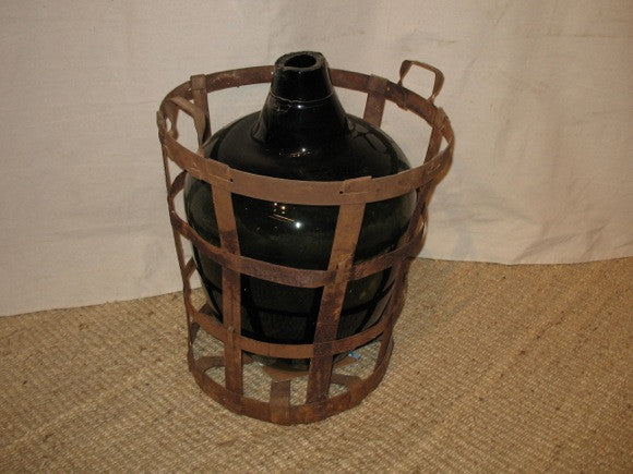 vintage european round wine bottle in iron basket