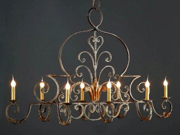 Fleur de Lis chandelier of iron with distressed antique finish and eight candles
