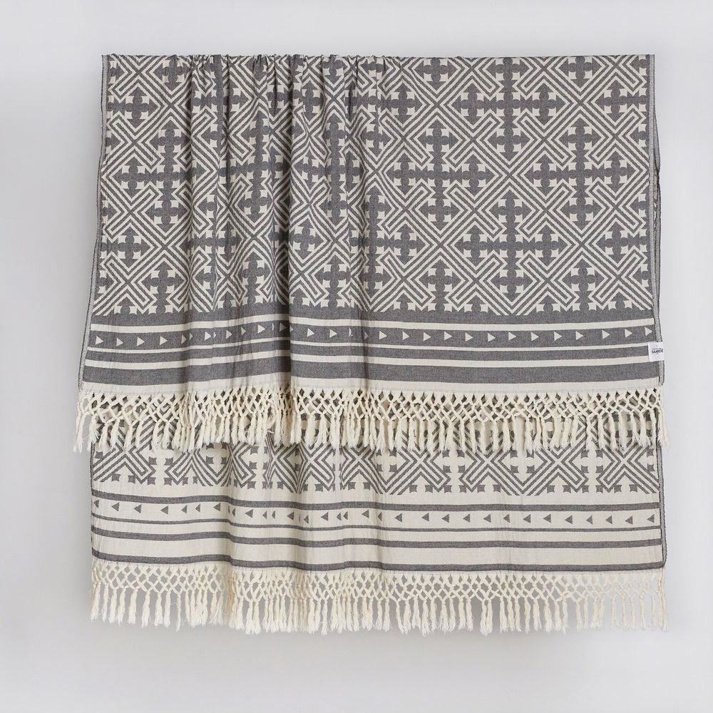 Traditional Jacquard Throw with a geometric pattern and fringed edge detail in a graphic black and cream tone.