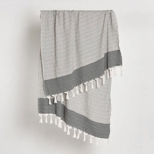 Traditionally hand loomed Turkish Towel with a fine stripe and geometric band on each end, in neutral grey and natural tones with a fringed edge detail.