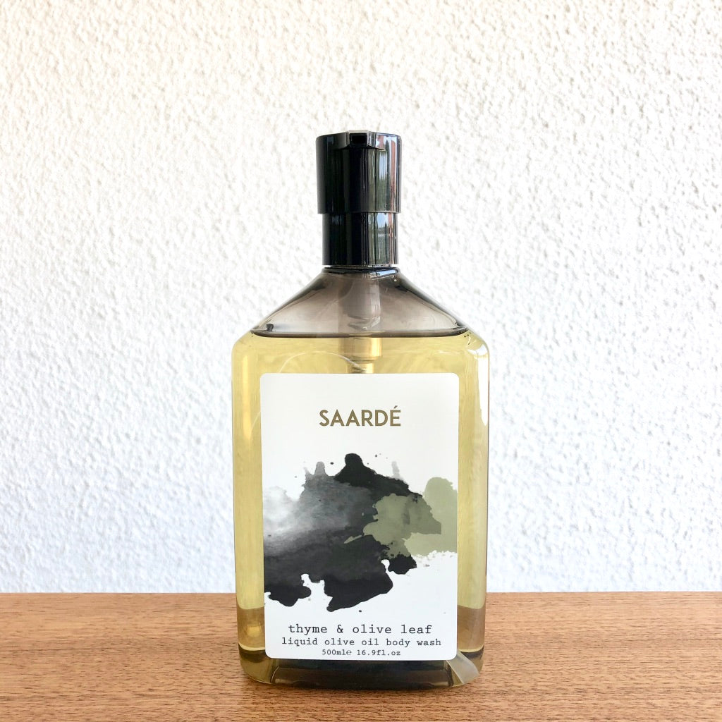 Thyme and Olive Leaf Liquid Olive Oil Body Wash is packaged beautifully in a smoked pump bottle with artistic labels.