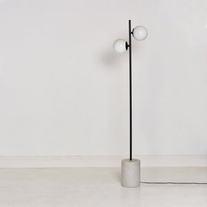 The Orb floor lamp features a rounded marble base floor lamp with black steel frame and handblown glass spheres to provide soft, diffused light.