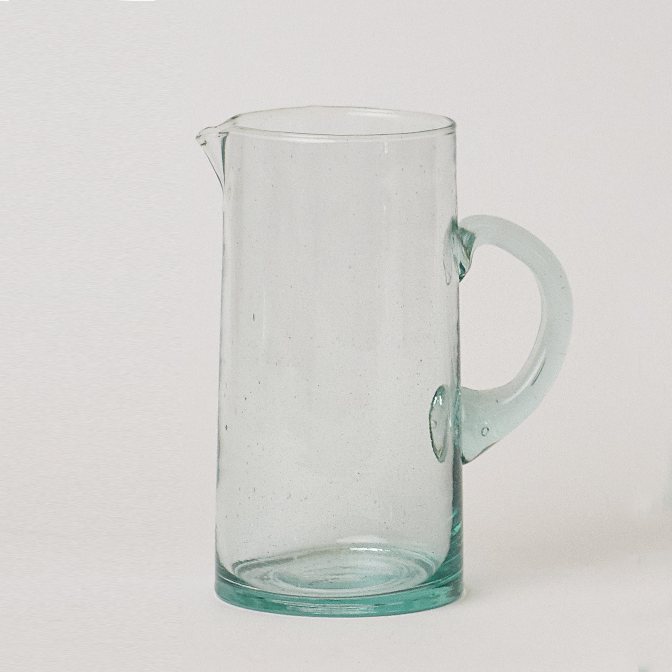 Hand blown Moroccan glass carafe with shaped spout and sturdy handle.  The one of a kind jug is a unique way to serve decorative drinks.