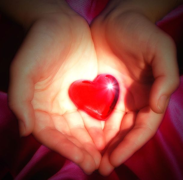 Red, glowing, heart-shaped stone held by two hands