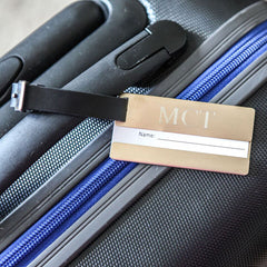 gold luggage tag with leather strap