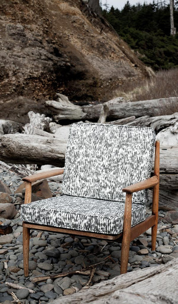 "Carley Kahn ""Stripe"" upholstery fabric. Upholstered chair in black and white colorway on rocky beach."