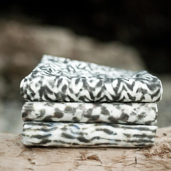 Carley Kahn upholstery fabrics. Three patterns folded and stacked on log.