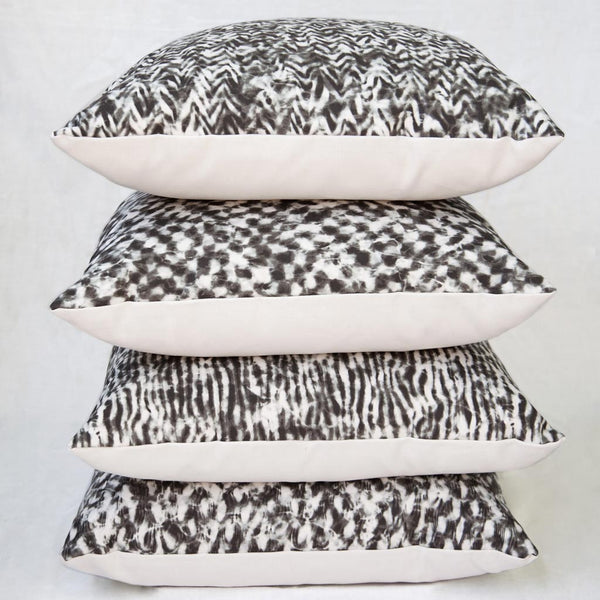 "Carley Kahn ""Checker"" pillow covers. Four of them stacked on top of each other."