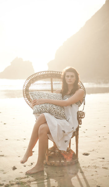 "Carley Kahn ""Checker"" pillow case. Model is sitting in peacock chair on beach and holding onto pillow."