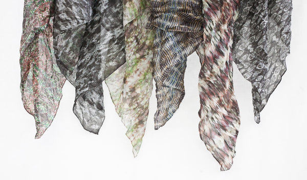 Carley Kahn silk scarves. Six of them hanging against white backdrop.