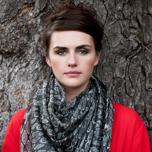 "Carley Kahn ""Ngawha Springs"" silk scarf. Model in red shirt wears scarf around neck while leaning against tree."