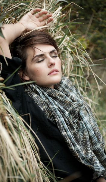 "Carley Kahn ""Abel Tasman"" silk scarf on model, dressed in black and reclining against a grassy hill with her eyes closed."