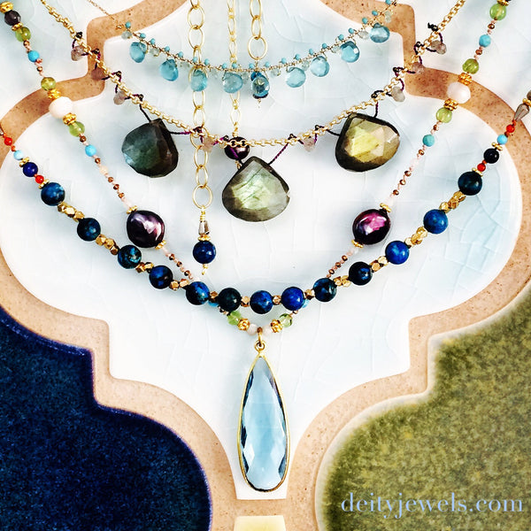 Blue Topaz charm necklace with Indigo Pearls, Aquamarine, Mother-of-Pearl, Peridot + Sleeping Beauty Turquoise, hand knotted on organic silk.