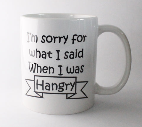 A white standard ceramic mug saying 'I'm sorry for what I said when I was Hangry'