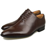 Men's wholecut semi-brogue shoes in brown faux leather both at an angle facing left
