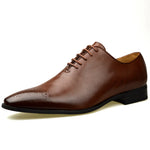Men's wholecut semi-brogue shoe in tan faux leather at an angle facing left