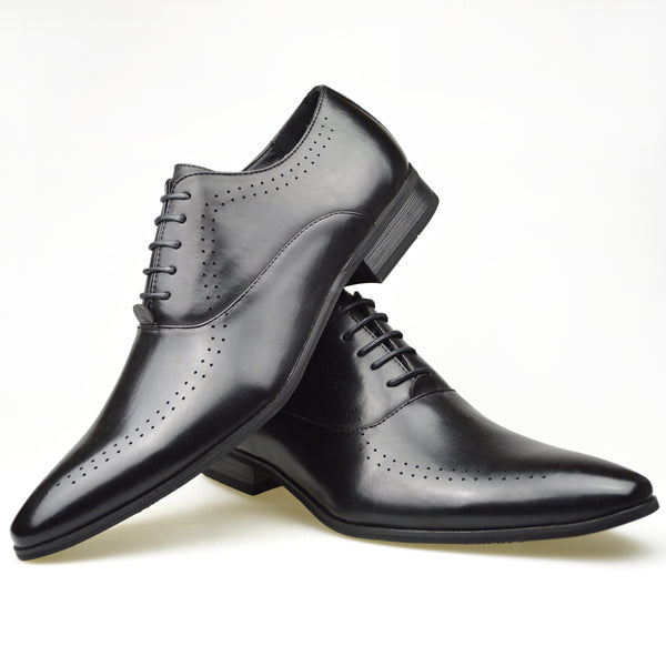 Men's perforated Oxford shoes in black faux leather placed one on top of the other