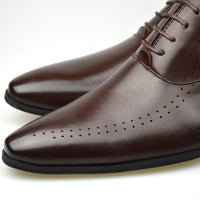 Close up of men's perforated Oxford shoes in brown faux leather with flowing perforation
