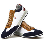 Men's slimline trainers in white faux suede leather placed one on top of the other