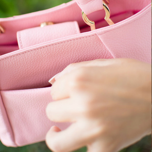 Pink pebbled leather Halo by HALOTOPIA small top handle tote bag with a slip pocket for essentials on the back of the bag. Featuring signature HALOTOPIA gold toned handbag hardware.
