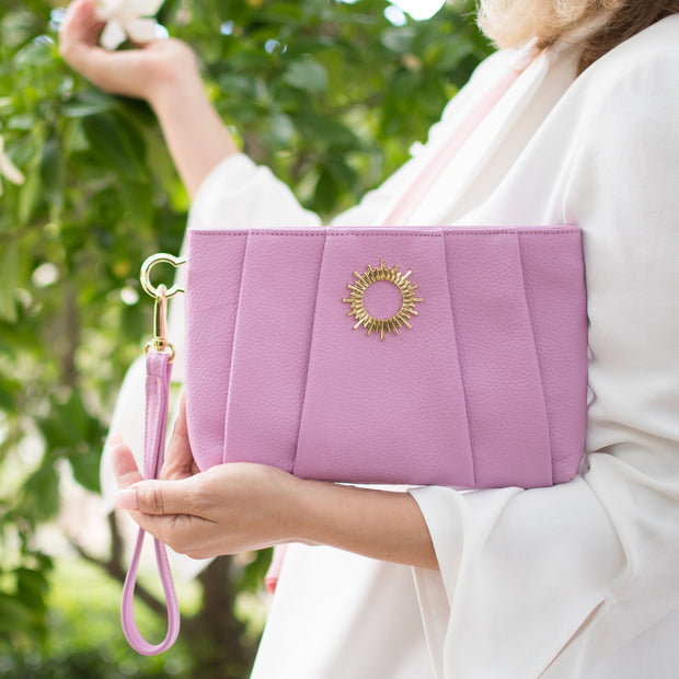 Halo by HALOTOPIA wristlet clutch bag in lavender color with pleated leather design and featuring HALOTOPIA gold toned hardware and the Halo by HALOTOPIA symbol. Removable wristlet strap included. to be worn as a wristlet or held as a clutch.