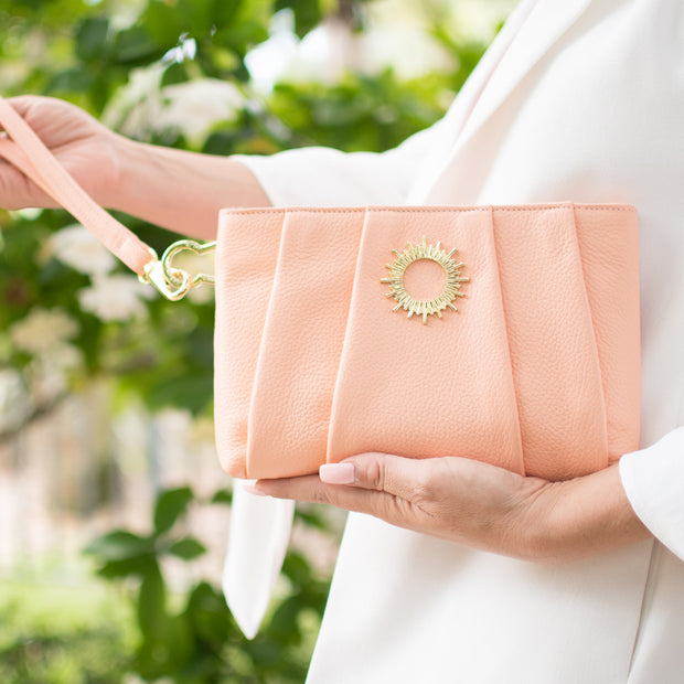 Halo by HALOTOPIA peach pleated leather wristlet clutch bag featuring HALOTOPIA gold toned handbag hardware and the original Halo by HALOTOPIA symbol. Including removable leather strap.