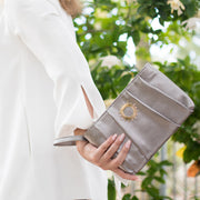Halo by HALOTOPIA silver pleated leather wristlet clutch bag featuring the original gold toned HALOTOPIA handbag hardware and the Halo by HALOTOPIA symbol. Removeable wristlet strap.