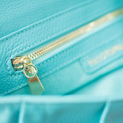 Interior detail of the interior zippered pocket inside the Halo by HALOTOPIA teal pebbled leather clutch bag with original gold toned HALOTOPIA hardware