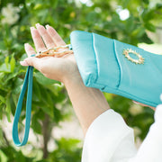 Halo by HALOTOPIA teal pleated pebbled leather wristlet with removable wristlet strap. Featuring the gold toned Halo by HALOTOPIA symbol.