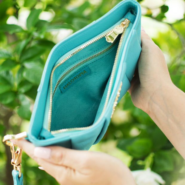 Interior detail of the Halo by HALOTOPIA teal leather wristlet. Zippered top closure with 1 interior zippered pocket and suede textured micro fiber interior lining.
