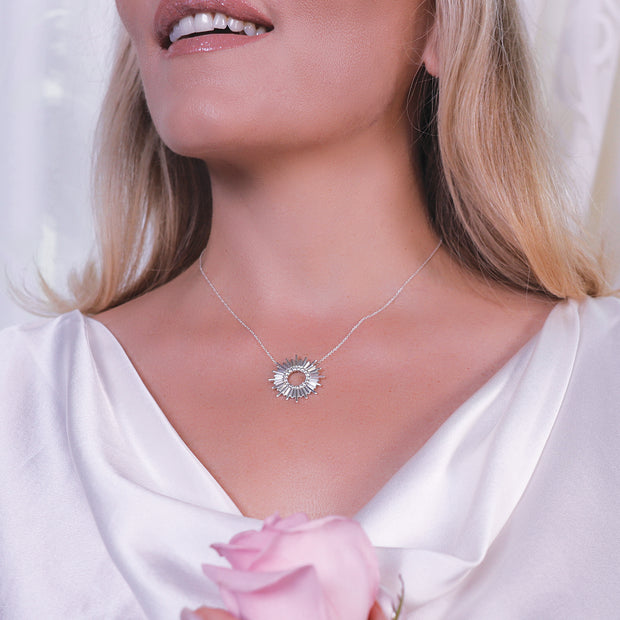 Woman wearing the Infinity Halo by HALOTOPIA pendant necklace in sterling silver with a circular array of white sapphires in the open center