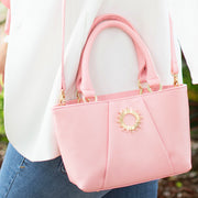 Pink colored Halo by HALOTOPIA small leather top handle tote bag featuring the Halo by HALOTOPIA symbol with pleated front leather design and signature HALOTOPIA gold toned hardware