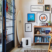 This subwoofer by Sonos is placed beside a bookshelf, demonstrating its flexible placement