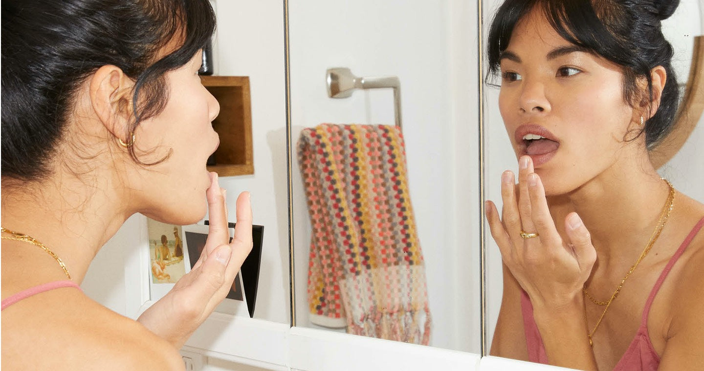 Woman looking into a mirror taking care of her skin by applying something to her face.