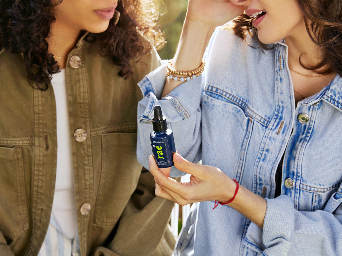 Two women sitting outdoors sharing Rae CBD drops. One woman is wearing a blue jean jacket and some wristbands and the other is in a mustard brown jean jacket with a white shirt underneath listening to the other individual explain something.