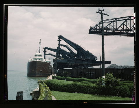 "Pennsylvania R.R. Railroad ore docks unloading iron ore from a lake freighter by means of ""Hulett"" unloaders Cleveland Ohio"